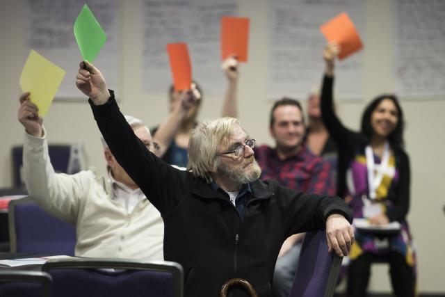 Researchers raising their hands at a conference